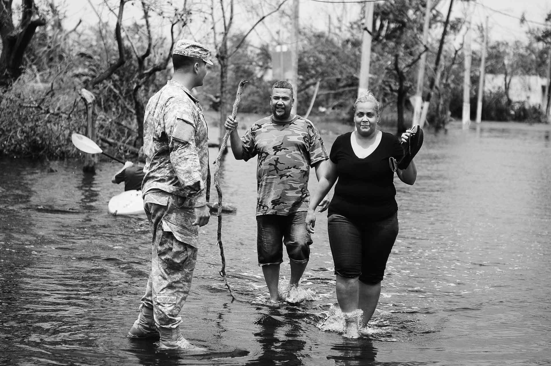 Puerto Rico National Guard Soldier helps a couple getting away from the flooded areas in Condado, San Juan, Puerto Rico after the path of Hurricane Maria. Photo by Sgt. Jose Ahiram Diaz-Ramos/PRNG-PAO